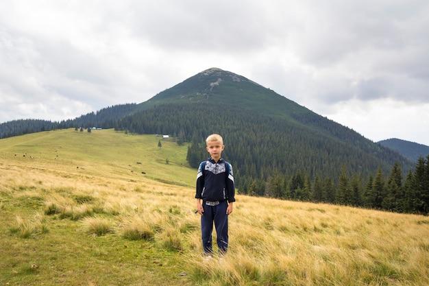 Młoda szczęśliwa uśmiechnięta dziecko chłopiec z plecak pozycją w halnym trawiastym dolina stylu