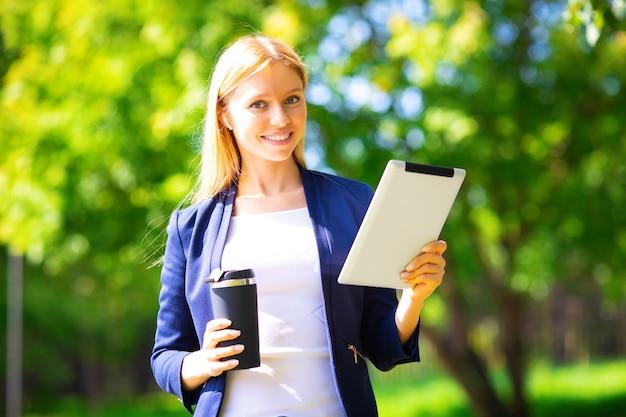 Młoda szczęśliwa uśmiechnięta kaukaski sukces dorosła dziewczyna spacerująca w parku z tabletem i telefonem