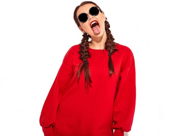 Młoda szczęśliwa uśmiechnięta kobieta model z jasnym makijażem i kolorowe usta z dwoma warkoczami i okulary w letnie czerwone ubrania na białym tle. pokazując jej język