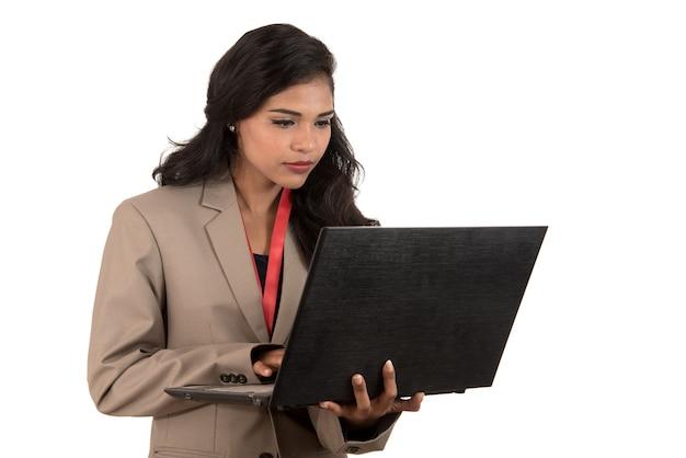 Młoda szczęśliwa uśmiechnięta kobieta trzyma laptop.