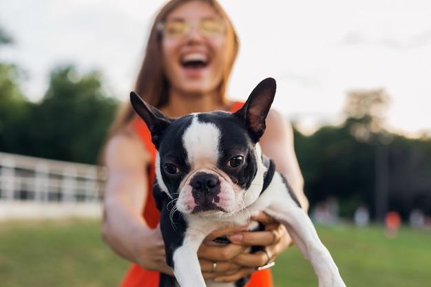 Młoda szczęśliwa uśmiechnięta kobieta trzyma psa boston terrier w parku, letni słoneczny dzień, wesoły nastrój, zabawa ze zwierzakiem, machanie długimi włosami, zabawa, letni trend w modzie