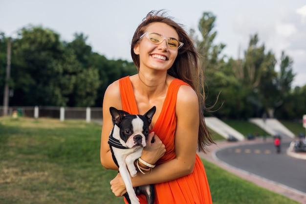 Młoda szczęśliwa uśmiechnięta kobieta trzyma psa boston terrier w parku, letni słoneczny dzień, wesoły nastrój, zabawa ze zwierzakiem, uściski, na sobie pomarańczową sukienkę, okulary przeciwsłoneczne, letni styl