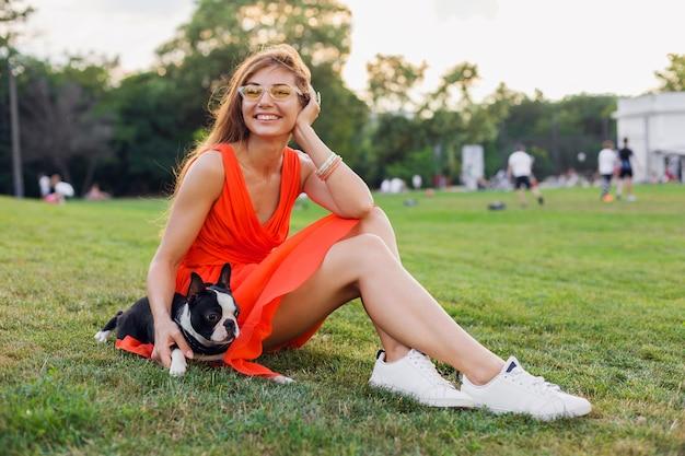 Młoda szczęśliwa uśmiechnięta kobieta w pomarańczowej sukience zabawy z psem w parku, styl lato, wesoły nastrój