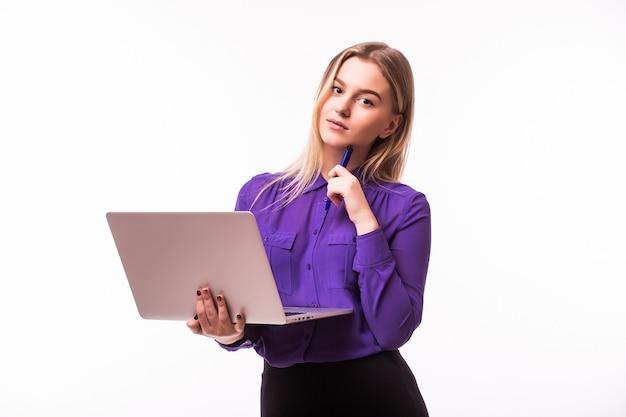 Młoda szczęśliwa uśmiechnięta kobieta w ubranie trzyma laptopa i wysyła e-mail do swojego najlepszego przyjaciela