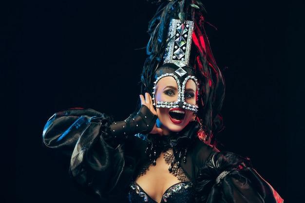 Młoda szczęśliwa uśmiechnięta piękna tancerka z karnawałowymi sukienkami pozuje na czarnym tle studyjnym