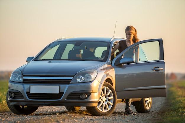 Młoda szczupła atrakcyjna kobieta o długich włosach w dżinsach i koszulce w srebrnym samochodzie z otwartymi drzwiami na pustej drodze żwirowej na jasne, jasne niebo, miejsce
