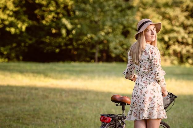 Młoda, szczupła, blond kobieta na rowerze przed niewyraźnym parkiem krajobrazu. jesienny odcień.