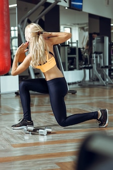 Młoda szczupła blond kobieta robi ćwiczenia w siłowni