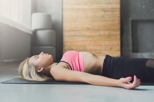 Młoda szczupła blond kobieta w zajęciach jogi leżała na podłodze. dziewczyna robi medytację zwłok, savasana dla relaksu. zdrowy tryb życia w centrum fitness. zbliżenie