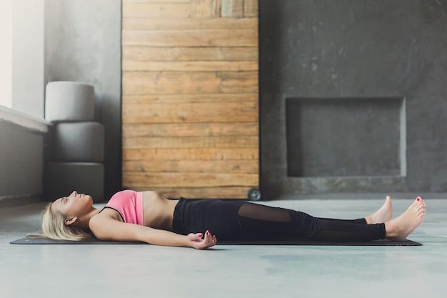 Młoda szczupła blond kobieta w zajęciach jogi leżała na podłodze. dziewczyna robi medytację zwłok, savasana dla relaksu. zdrowy tryb życia w centrum fitness