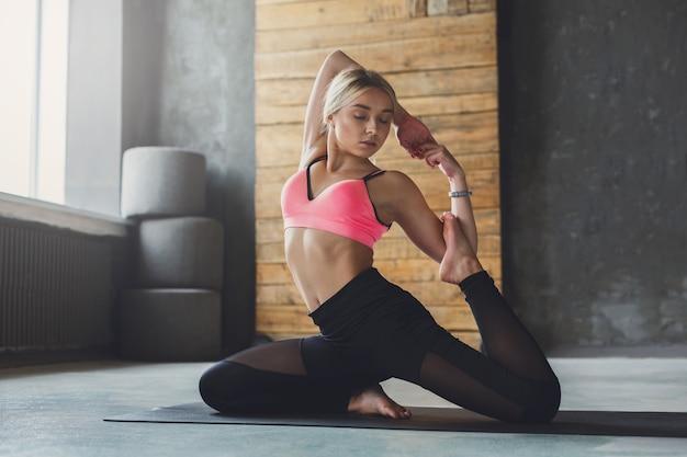 Młoda szczupła blond kobieta w zajęciach jogi wykonywanie pięknych ćwiczeń asan. kobieta w pozie syreny, odmiana rajakapotasana. zdrowy styl życia w klubie fitness. rozciąganie