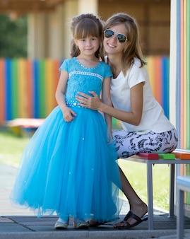 Młoda szczupła blond uśmiechnięta matka, ciocia lub siostra przytula małą ładną córkę w wieku przedszkolnym w długiej ładnej niebieskiej sukience wieczorowej na niewyraźne boisko