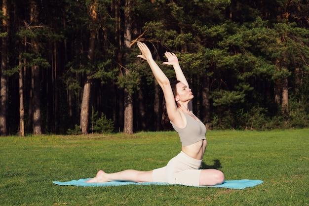 Młoda, szczupła dziewczyna ćwiczy jogę, wykonuje asany na macie, na łonie natury. sporty na świeżym powietrzu, koncepcja zdrowego stylu życia. kobieta spędza sesję fitness w parku, w lesie, na słońcu.