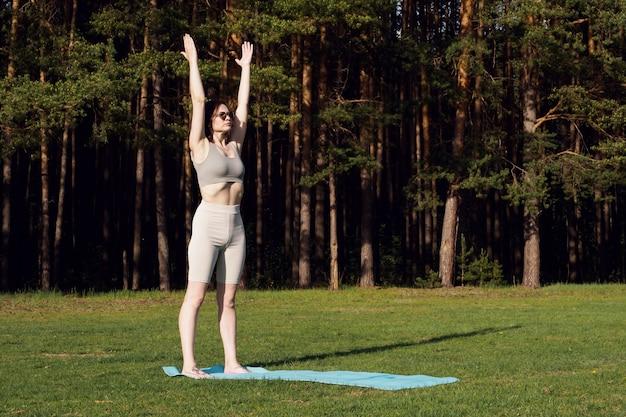 Młoda, szczupła dziewczyna ćwiczy jogę, wykonuje asany na macie, na łonie natury. sporty na świeżym powietrzu, koncepcja zdrowego stylu życia.