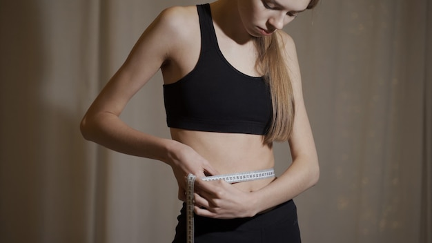 Młoda szczupła dziewczyna mierzy objętość swojej talii