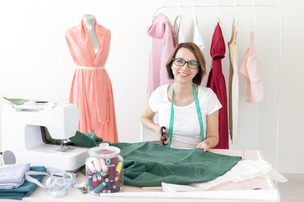Młoda, szczupła dziewczyna projektantka krawcowa w okularach siedzi przy biurku z nicią do szycia i przecina kawałek materiału do szycia nowych produktów. koncepcja warsztatu szycia.