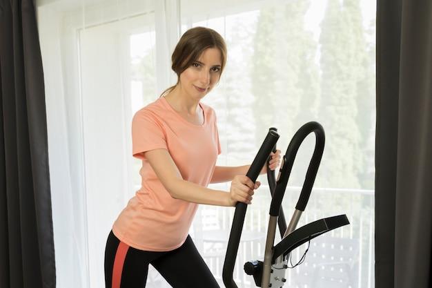 Młoda szczupła dziewczyna uprawia sport w domu. koncepcyjne zdjęcie przedstawiające zalety sportu i zdrowego stylu życia.
