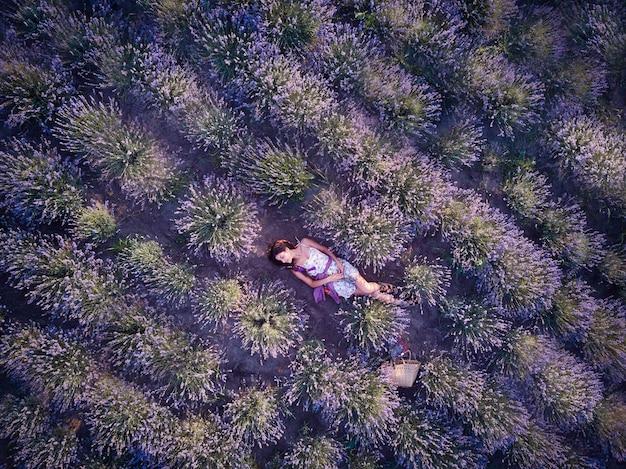 Młoda szczupła jasnoskóra dziewczyna brunetka piękna leży w lawendowym polu. widok z góry.