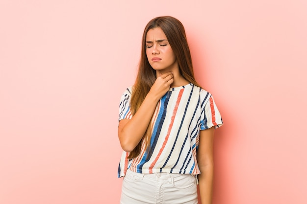 Młoda szczupła kobieta cierpi na ból gardła z powodu wirusa lub infekcji.