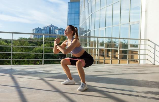 Młoda szczupła kobieta ćwicząca z gumkami fitness na świeżym powietrzu w mieście