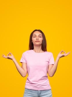 Młoda szczupła kobieta gestykuluje gyan mudra i oddycha z zamkniętymi oczami podczas medytacji na żółtym tle