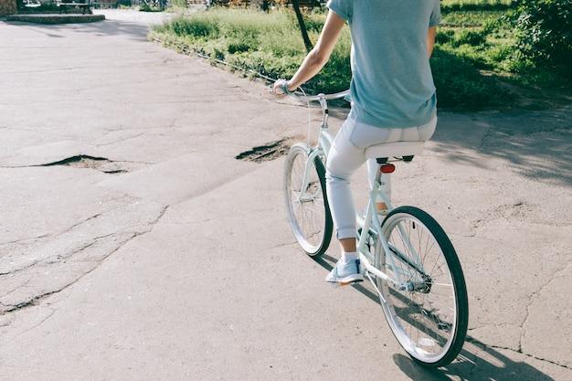 Młoda szczupła kobieta jeździ po mieście na rowerze