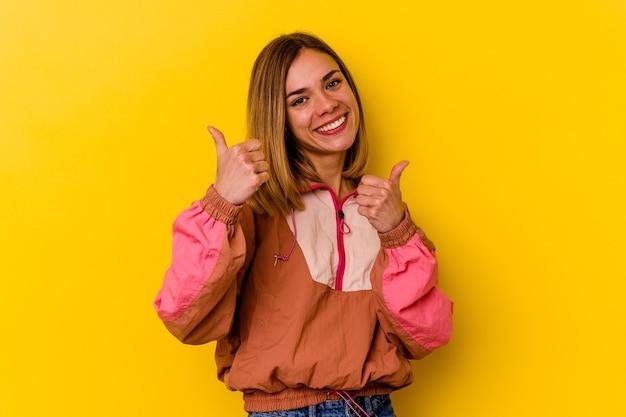 Młoda szczupła kobieta kaukaski na białym tle na żółtym tle, podnosząc kciuki do góry, uśmiechnięta i pewna siebie.
