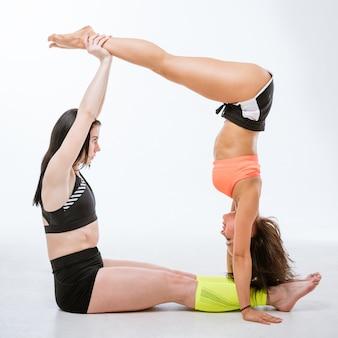 Młoda szczupła kobieta lekkoatletycznego robi gimnastykę na białym tle