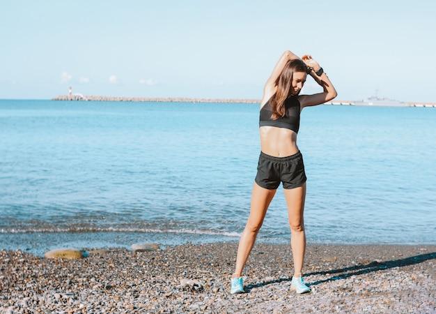Młoda szczupła kobieta lekkoatletycznego w odzieży sportowej, ćwiczenia na plaży rano