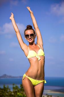 Młoda szczupła kobieta o niesamowitym ciele, pozująca na egzotycznej tropikalnej wyspie tajlandii, w trybie wakacyjnego relaksu, w modnym bikini i okularach przeciwsłonecznych, w trybie wakacyjnym, w stonowanych kolorach.
