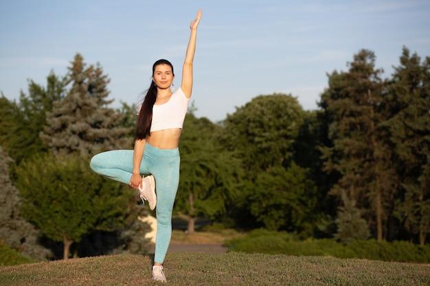 Młoda szczupła kobieta robi ćwiczenia jogi na tle lasu. miejsce na tekst