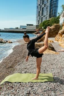 Młoda szczupła kobieta robi ćwiczenia mięśni na macie do jogi na zewnątrz przy kamienistej plaży nad morzem