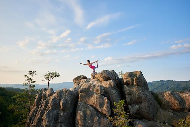 Młoda szczupła kobieta robi skomplikowaną pozę do jogi na oświetlone latem słońce na szczycie wielkiej skały na zielonych drzewach i jasne tło błękitnego nieba rano. koncepcja fitness i zdrowego stylu życia.