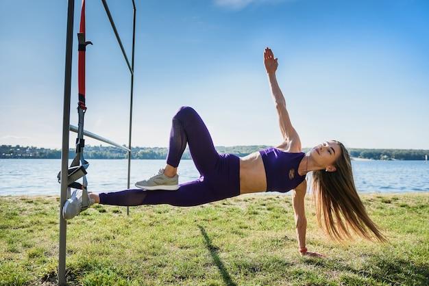 Młoda szczupła kobieta robi trening zawieszenia z pasami fitness na zewnątrz