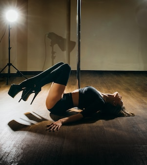 Młoda szczupła kobieta sexy taniec na rurze na ciemnym tle ze światłami