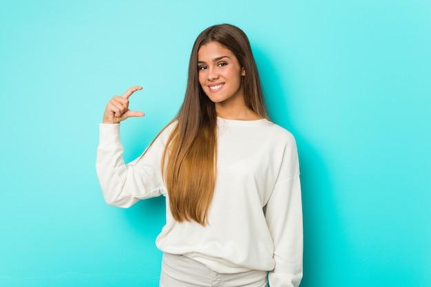 Młoda szczupła kobieta trzyma coś małego z palcami wskazującymi, uśmiechnięta i pewna siebie.