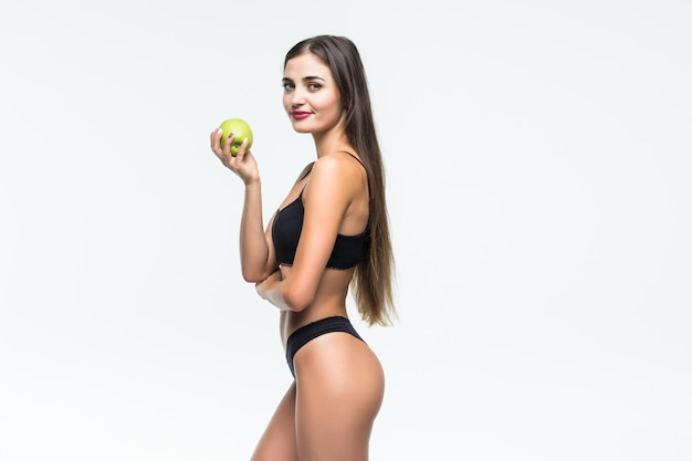 Młoda szczupła kobieta trzyma czerwone jabłko. na białym tle na białej ścianie. pojęcie zdrowej żywności a kontrola nadwagi.