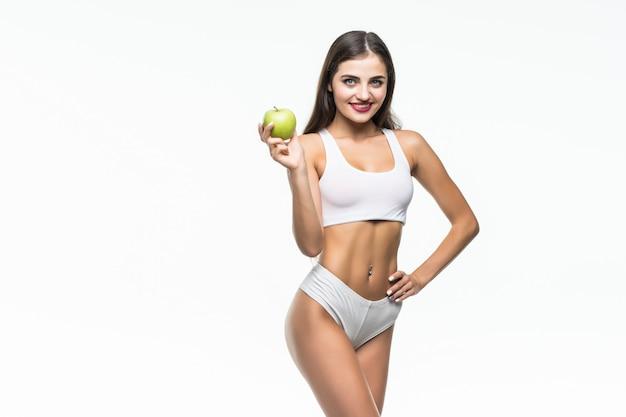 Młoda szczupła kobieta trzyma zielone jabłko. na białym tle na białej ścianie. pojęcie zdrowej żywności a kontrola nadwagi.