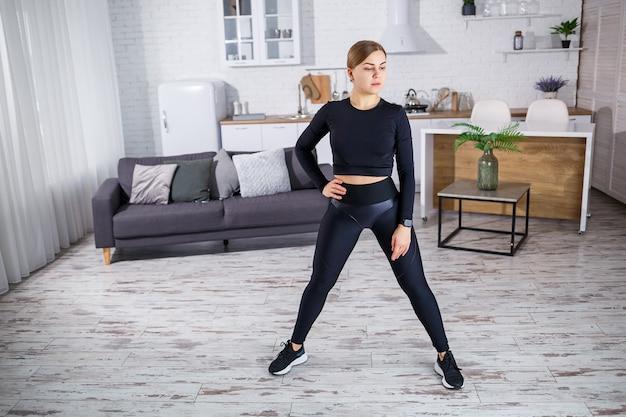 Młoda, szczupła kobieta uprawia sport w domu, ubrana w stroje fitness, czarną bluzkę i legginsy. fitness w domu dla pięknego ciała. rozgrzej się przed uprawianiem sportu