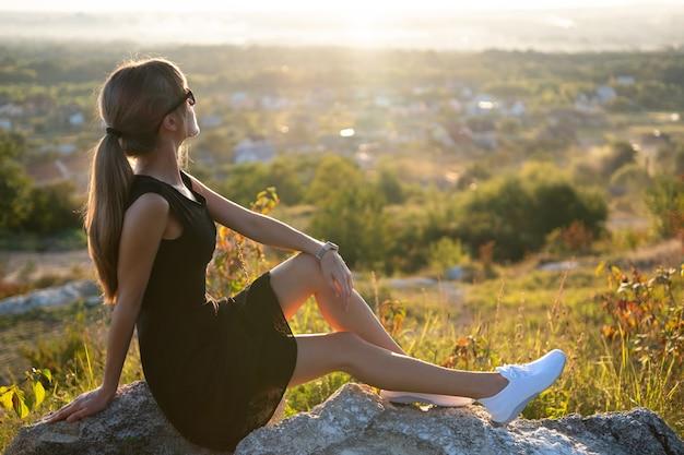 Młoda szczupła kobieta w czarnej krótkiej sukience siedzi na skale, relaks na świeżym powietrzu o zachodzie słońca latem.