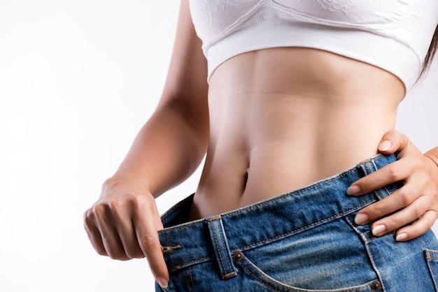 Młoda szczupła kobieta w dużych niebieskich dżinsach. dopasowana kobieta ma na sobie zbyt duże spodnie