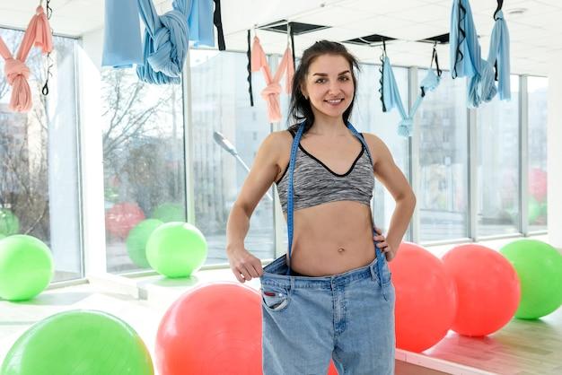 Młoda szczupła kobieta w górę pomiaru jej klatki piersiowej w siłowni fitness. pojęcie zdrowego stylu życia