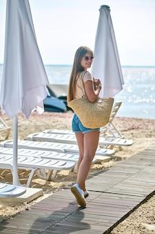 Młoda szczupła kobieta w krótkich spodenkach na plaży