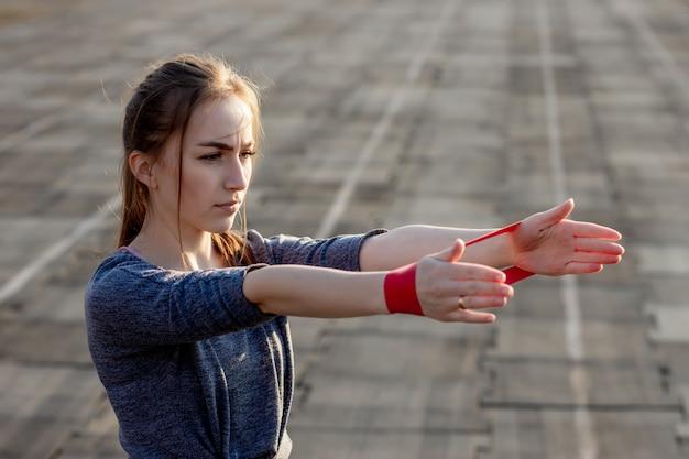 Młoda szczupła kobieta w odzieży sportowej robi przysiady ćwiczenia z gumką na torze stadionu powlekanego na czarno