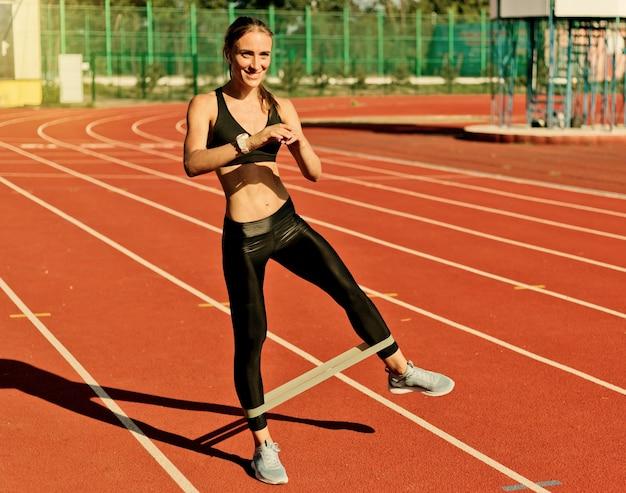 Młoda szczupła kobieta w sportowej robi ćwiczenia fitness z gumką na czerwonym torze stadionu powlekanym