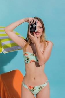 Młoda szczupła kobieta w strojach kąpielowych biorąc zdjęcie