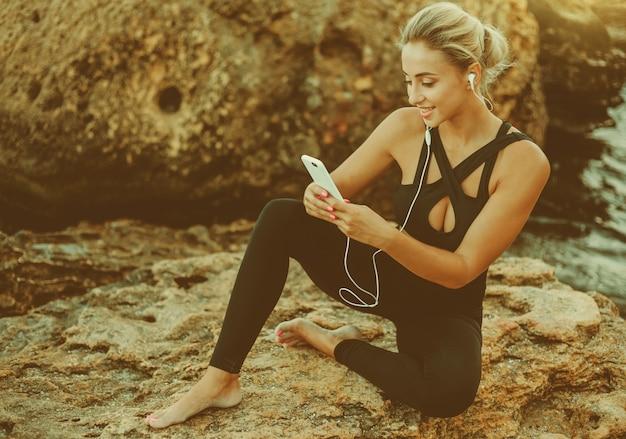 Młoda, szczupła kobieta w stroju sportowym, słuchająca muzyki w słuchawkach i korzystająca ze smartfona, siedząc na kamieniu na dzikiej plaży