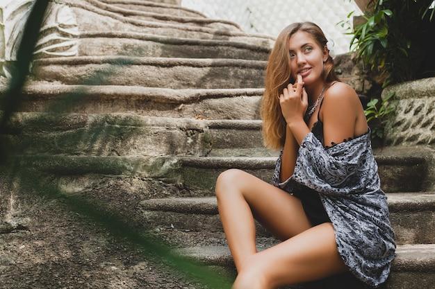 Młoda szczupła kobieta w tropikalnej willi bali, ubrana w seksowną bieliznę, zmysłową, piękną, zalotną, opaloną skórę, modną odzież, etniczny styl boho, koszulę nocną, pelerynę, naturalne piękno