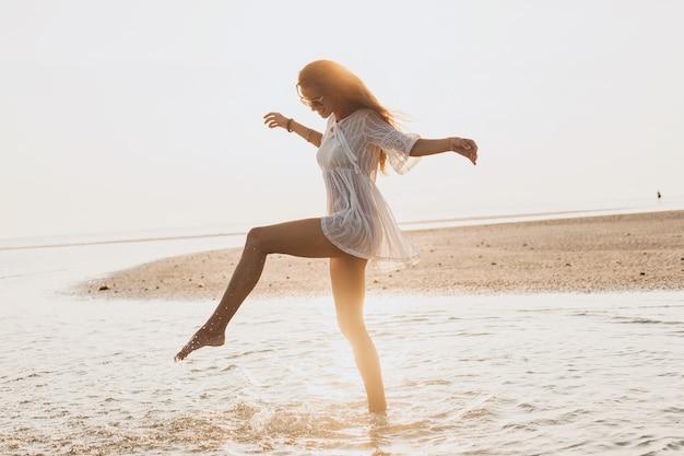 Młoda szczupła piękna kobieta na plaży o zachodzie słońca