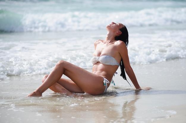 Młoda szczupła seksowna dziewczyna w bikini z latającymi włosami na kobiety brunetka w strój kąpielowy na piaszczystej plaży na tle fal
